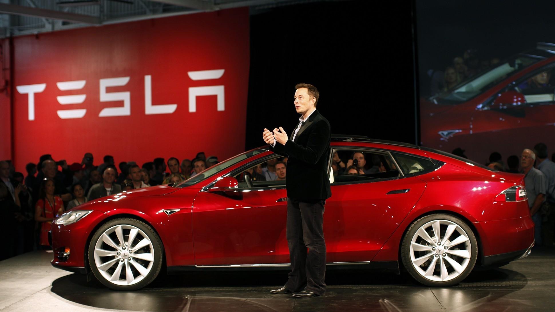 Elon Musk standing next to a Tesla Model S at a Press Event.