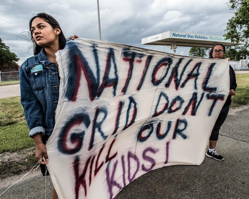 """image description: two people holding a fabric banner outside of National Grid's facility in Providence, RI. Sign reads: """"NATIONAL GRID DON'T KILL OUR KIDS!"""""""