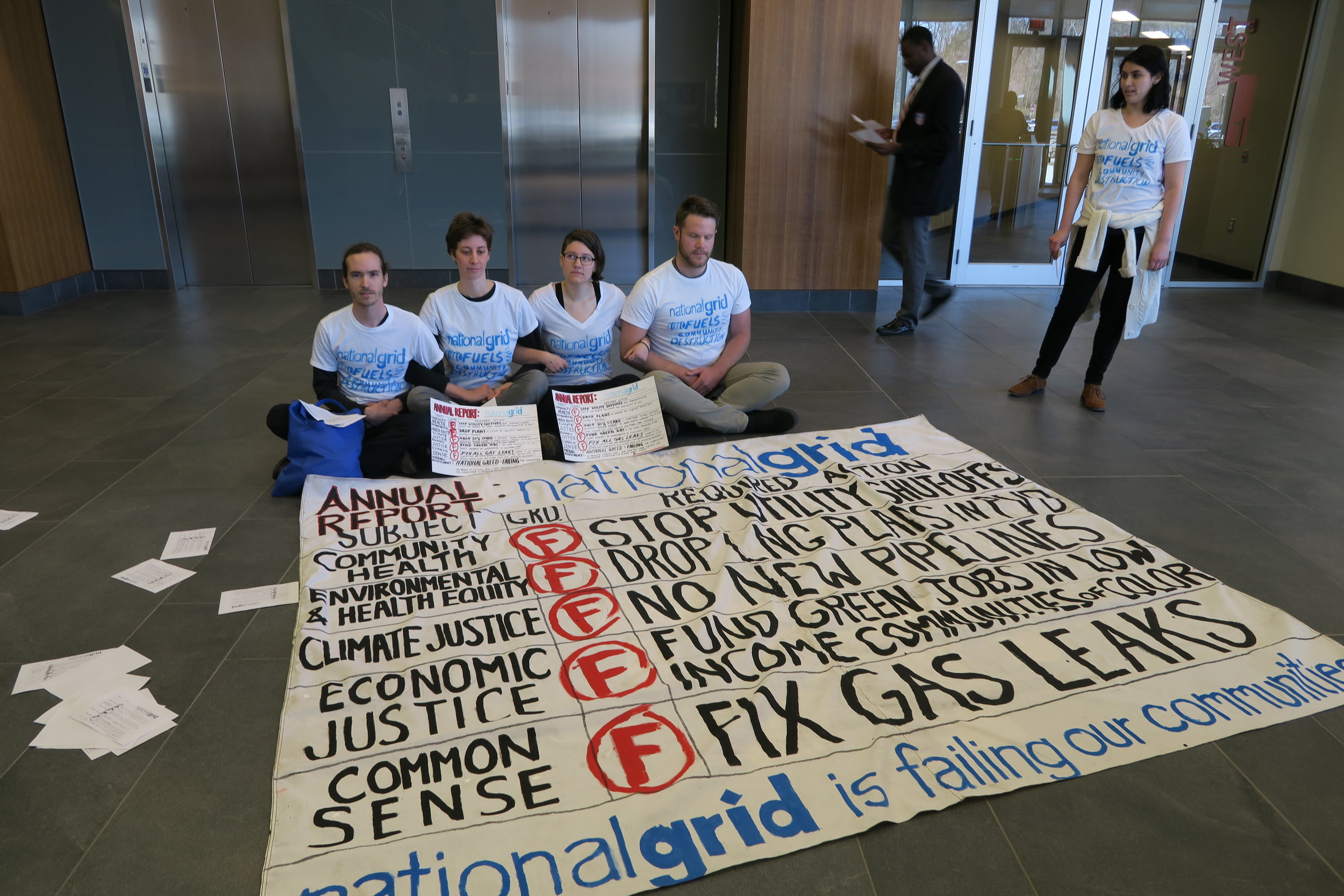 image description: 4 people with their arms linked sitting on the floor of National Grid's headquarters in Waltham, MA with a large fabric banner that replicates an annual report - failing National Grid in the areas of community health, environmental & health equity, climate justice, economic justice, and common sense.