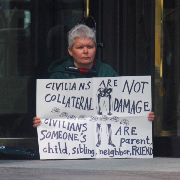 """photo by: RI Future  image description: FANG co-founder Pia Ward's neck is locked to the front door of Textron's headquarters in Providence, RI. She is holding a sign that reads: """"CIVILIANS ARE NOT COLLATERAL DAMAGE CIVILIANS ARE SOMEONE'S parent, child, sibling, neighbor, FRIEND"""