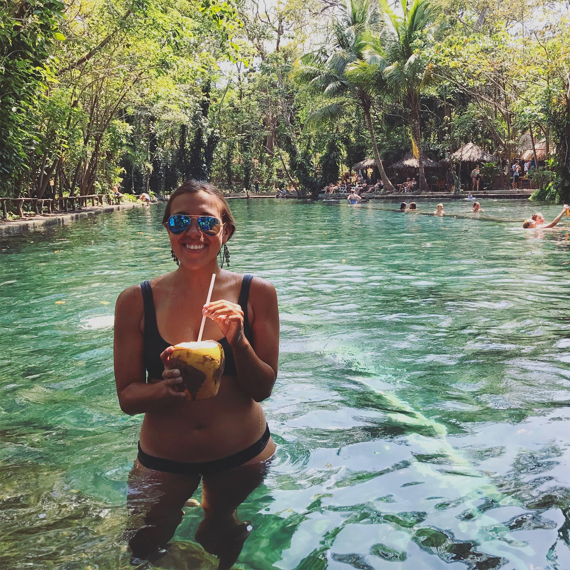 sapphire & elm travel co-founder, stephanie sipping on a coco loco at ojo de agua