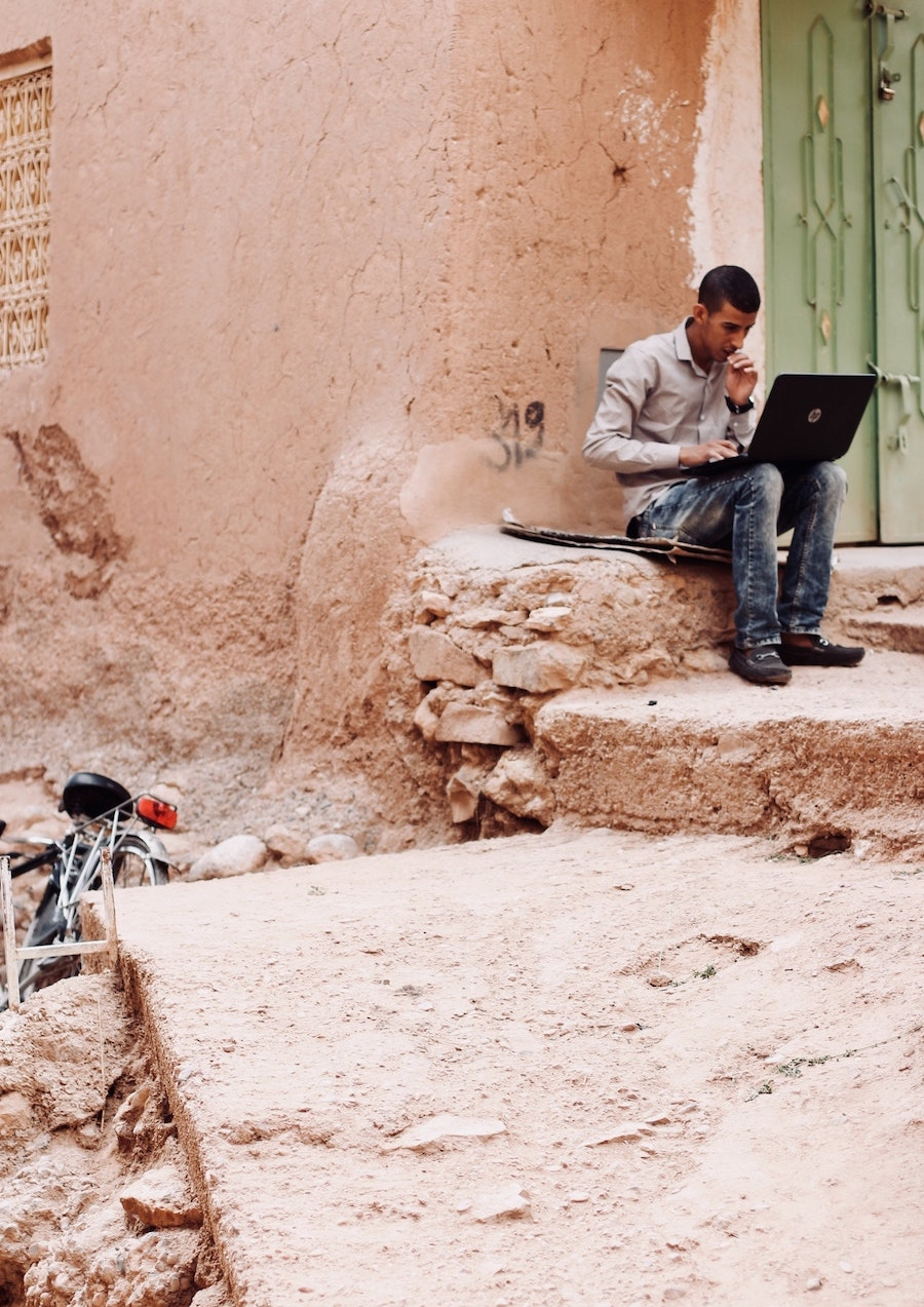 Marrakech man on laptop | The City that Inspired Fashion Icon, Yves Saint-Laurent Most