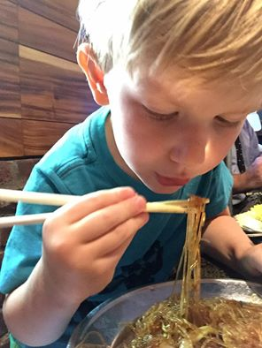 """Day two photo by challenge participant Key Rosebrook. Said Key, """"He was engrossed. Totally focused on eating my dinner. Focused on using the chopsticks. I like this photo because it captures the stolen moments (and food) of my life. I was glad to get he shot of our """"foodie in the making""""."""""""