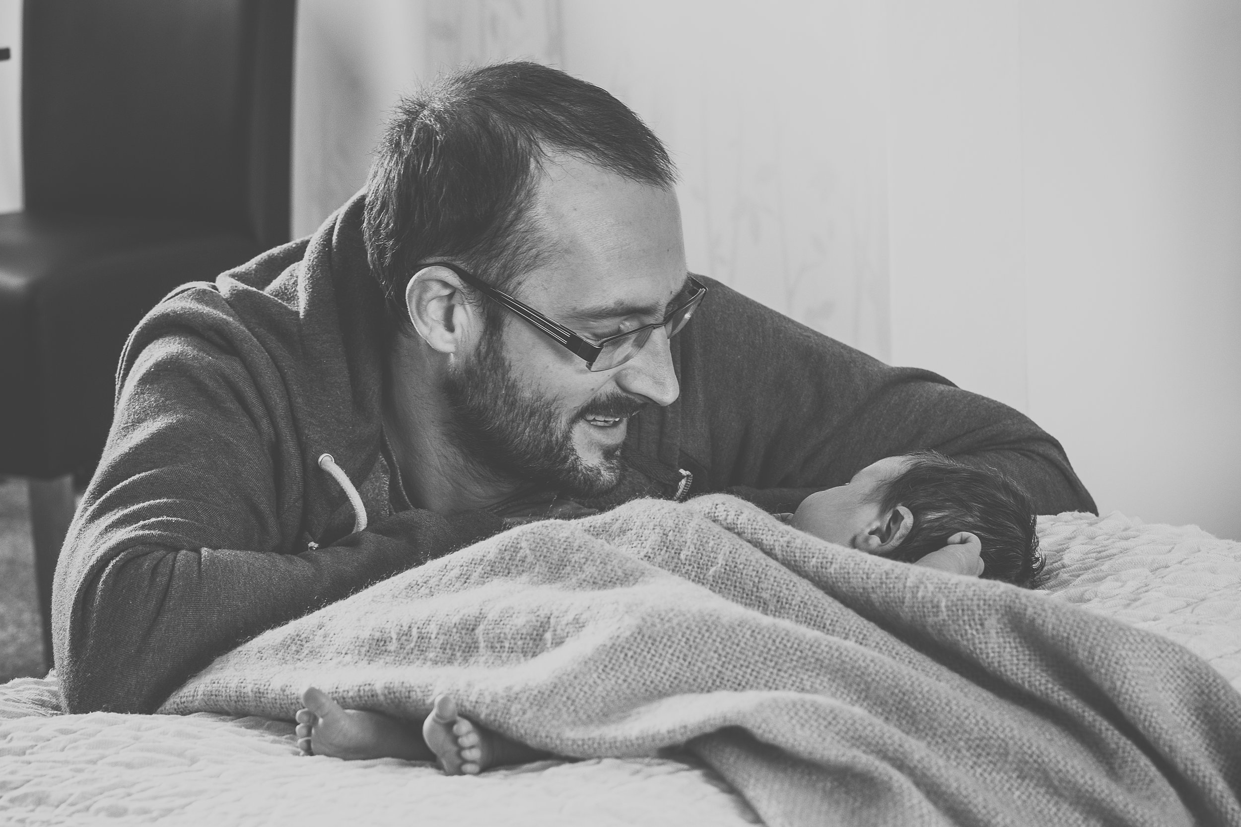 Black and white of new dad smiling at his newborn son