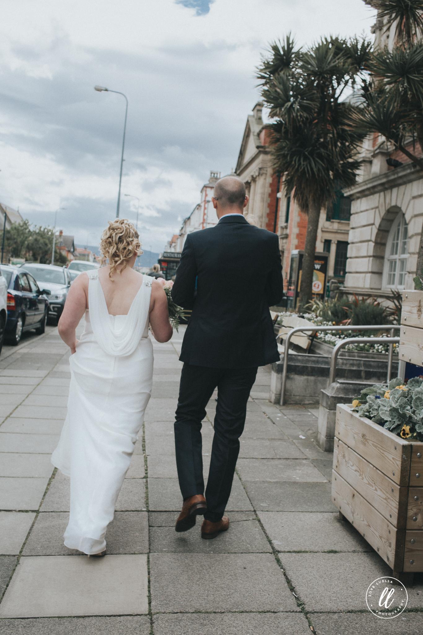The bride, groom and their son walk through llandudno town
