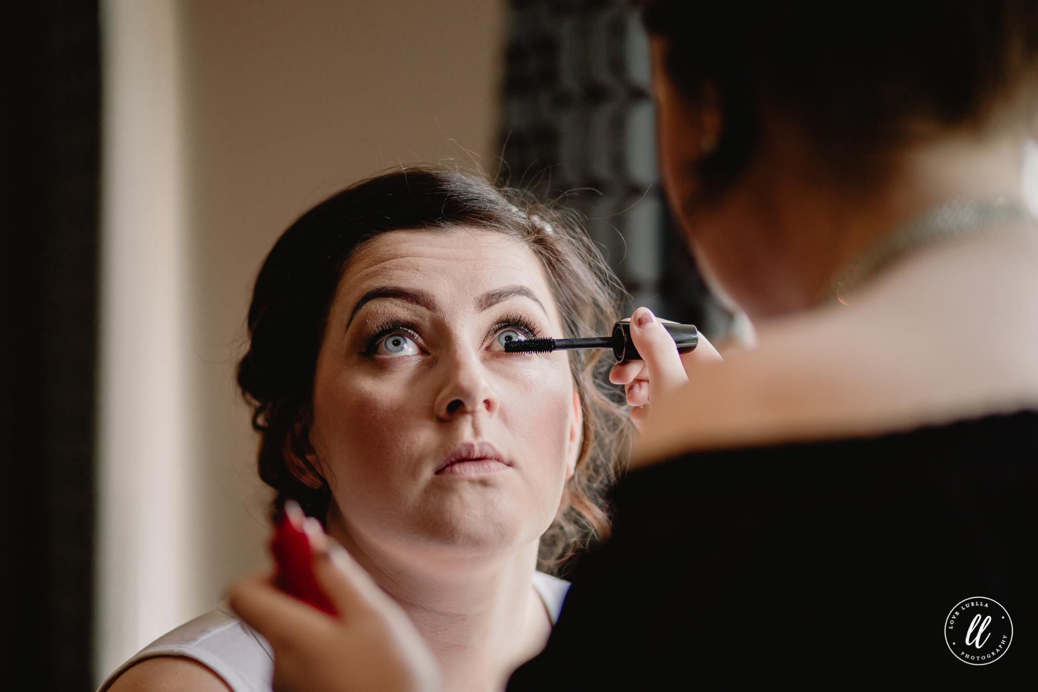 Mascara being applied to the bride near a window at The Kinmel
