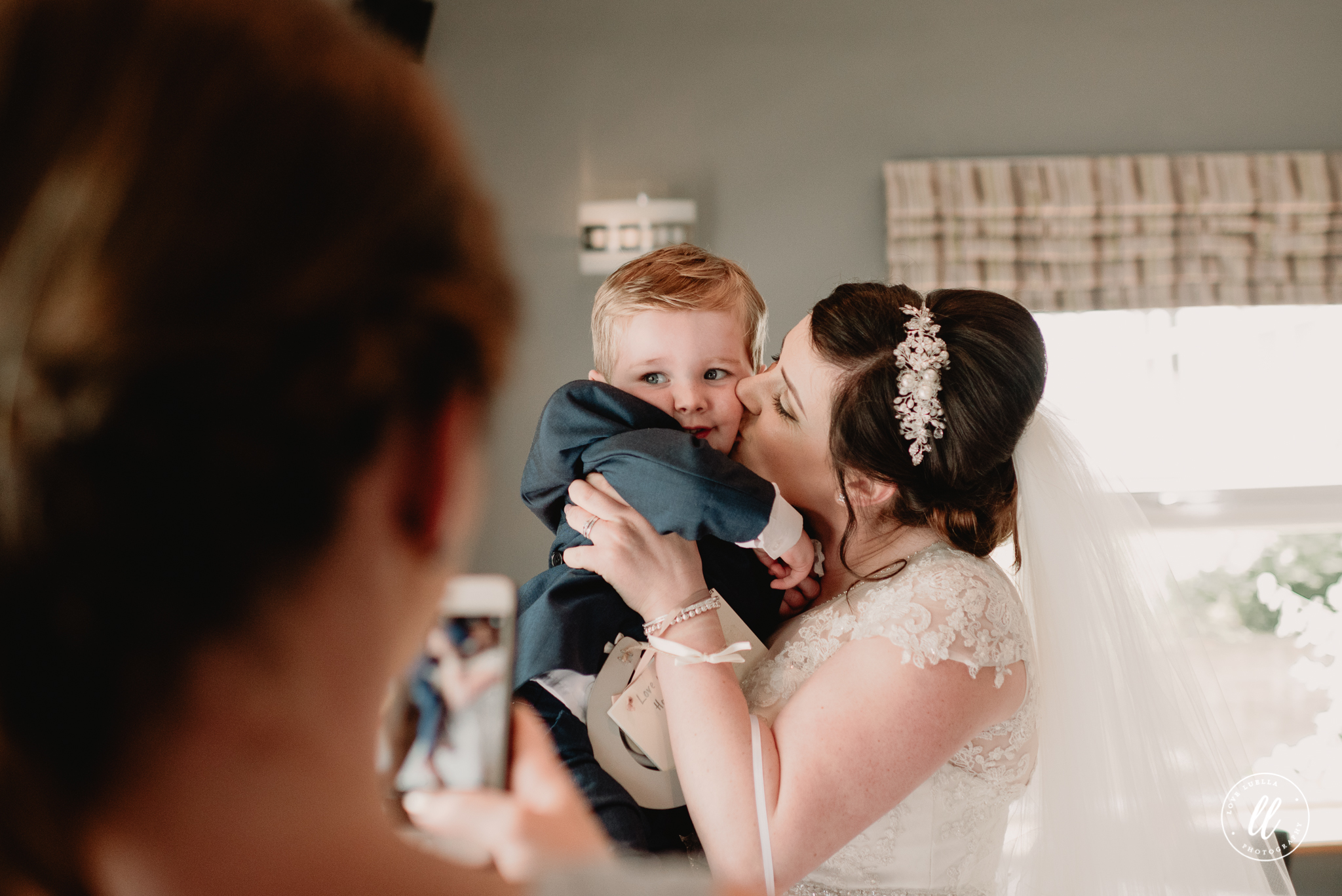 The bride holding her good friends baby and giving him a kiss