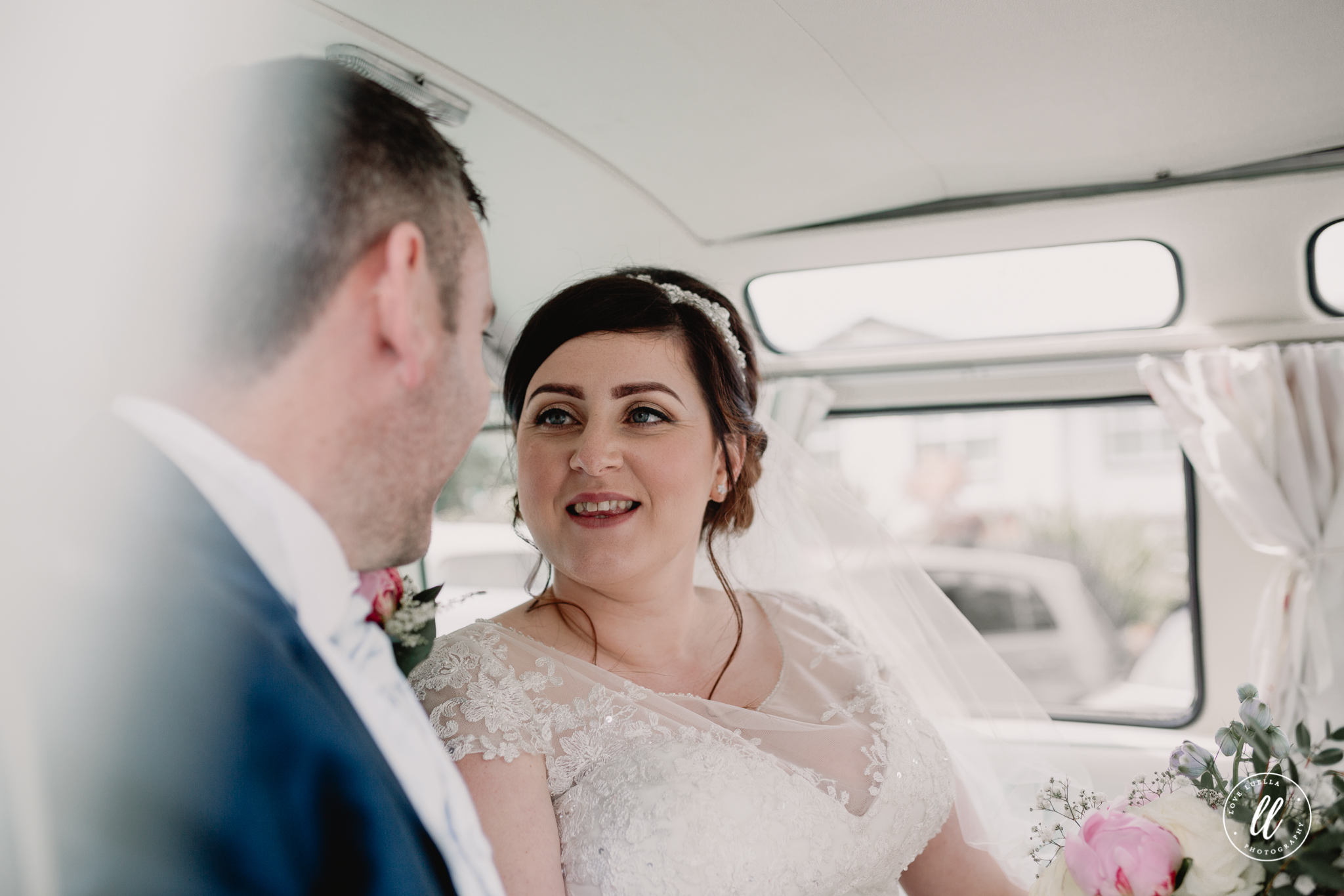 The bride looking at her husband with pride, sitting in their split the difference camper van