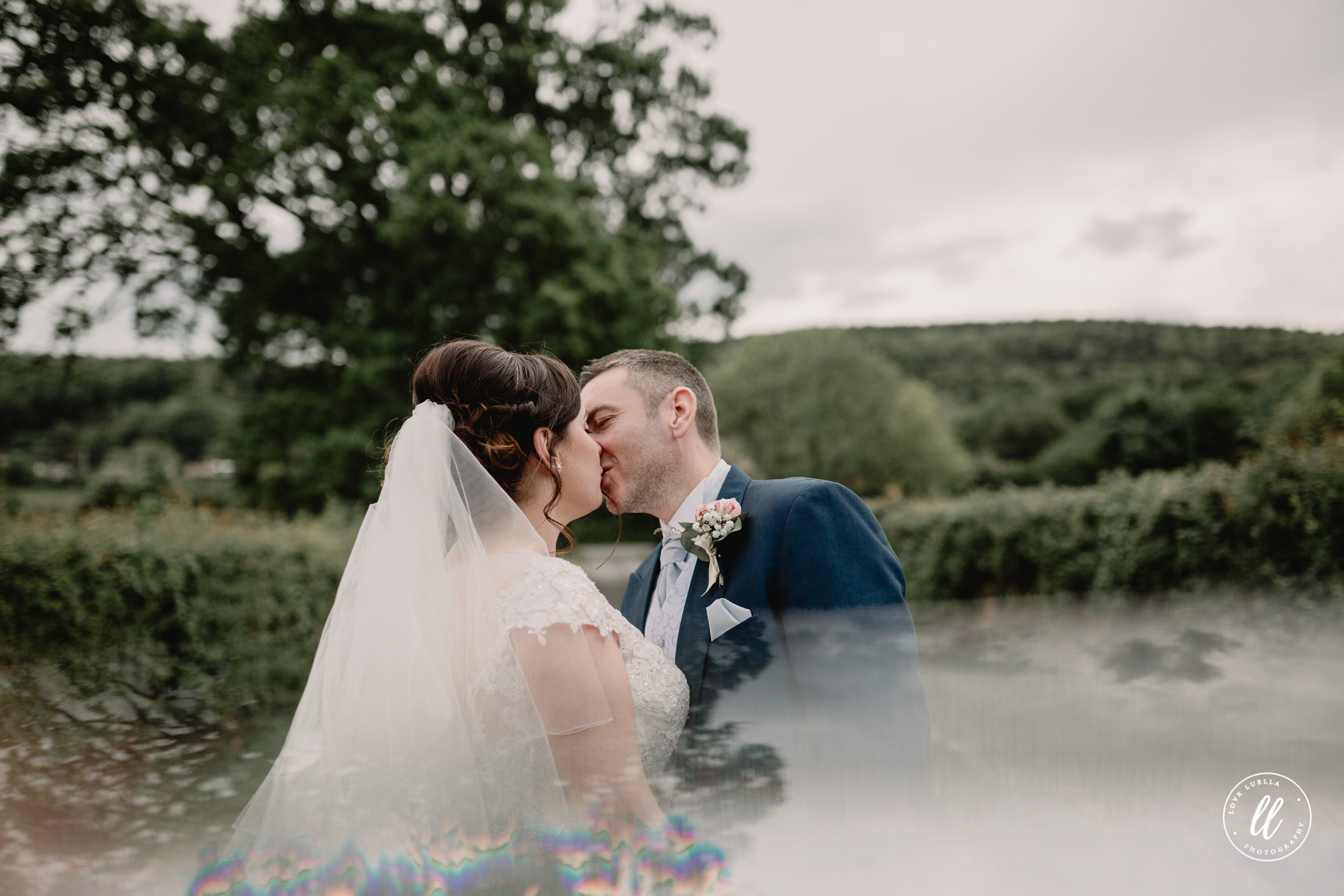 mr and mrs jones sharing a kiss outside the Kinmel Manor, image shot with a prism for a light effect
