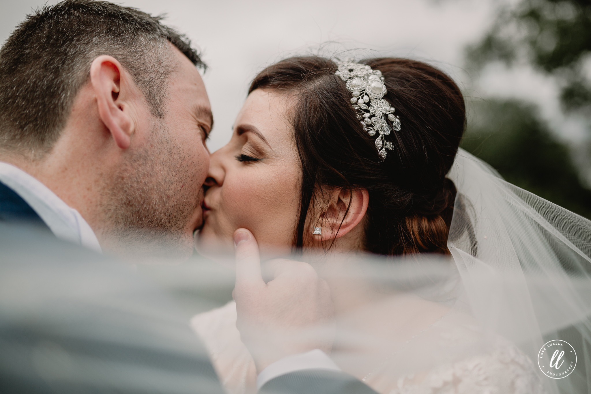 the bride and groom kissing, the grooms thumb resting on the brides cheek