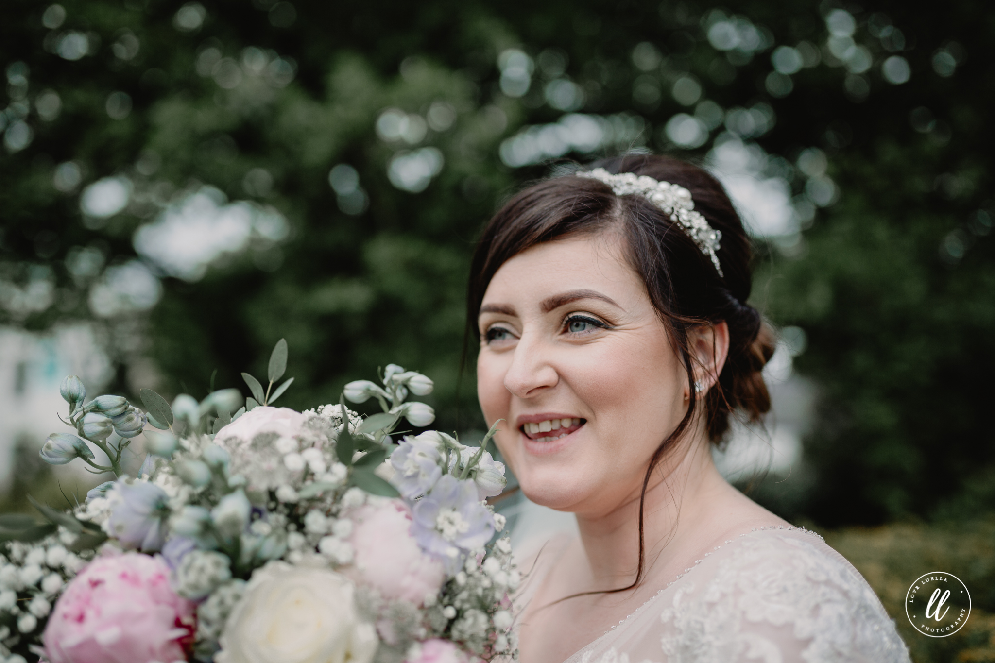 The bride laughing holding her bouquet close to her face