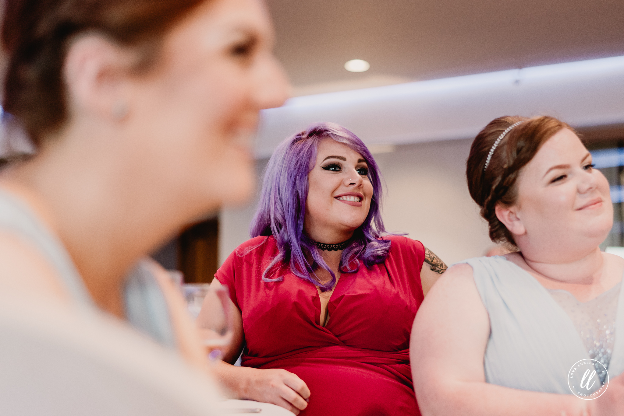 a guest with purple hair laughing along in a red dress