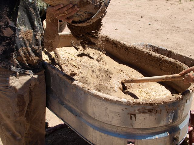 Volunteers mixing an adobe brick mix for a community project.