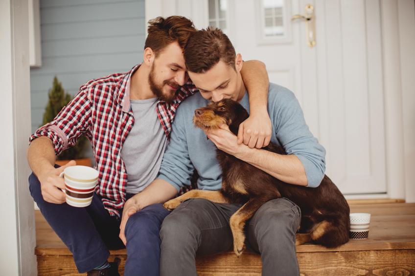 two men hugging holding a dog