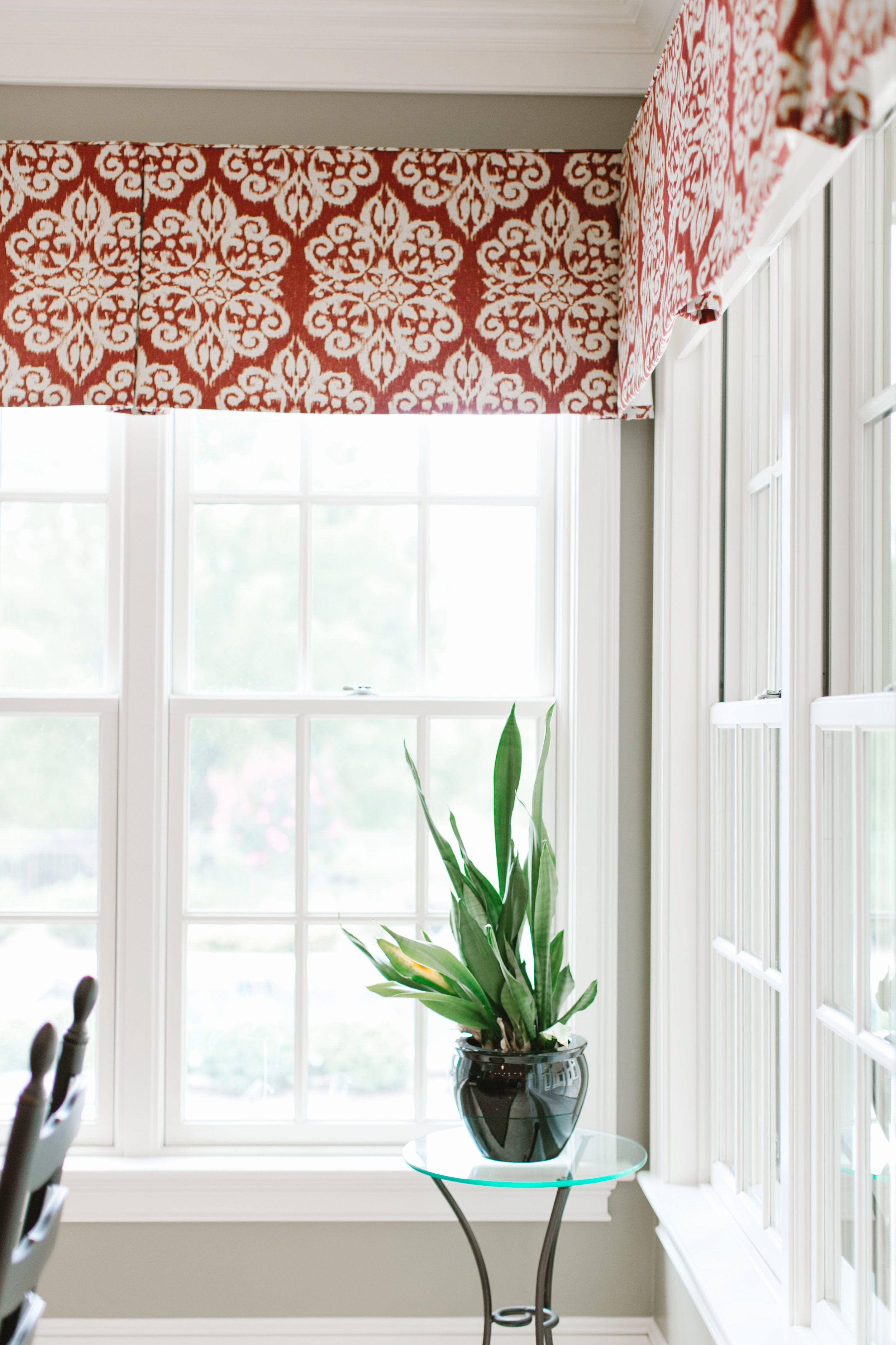 Red fabric valances bring color to a client's dining room
