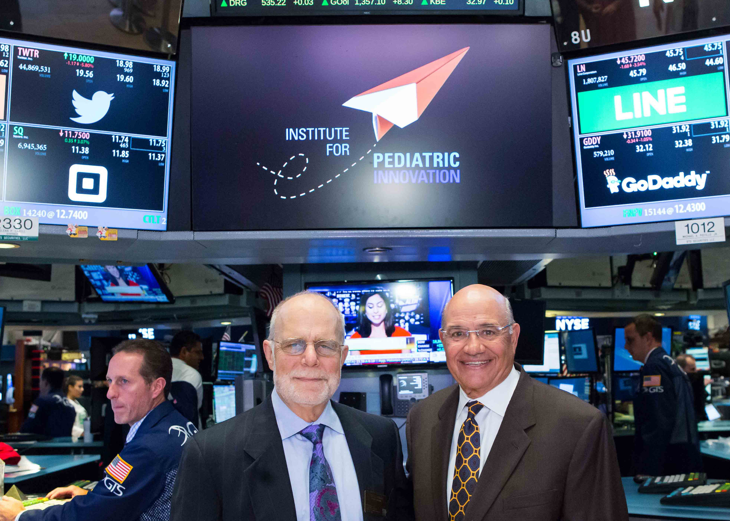 Founder Donald Lombardi (left) and President/CEO Stephen Evangelista pose in front of IPI's logo before ringing the New York Stock Exchange's closing bell in August of 2016