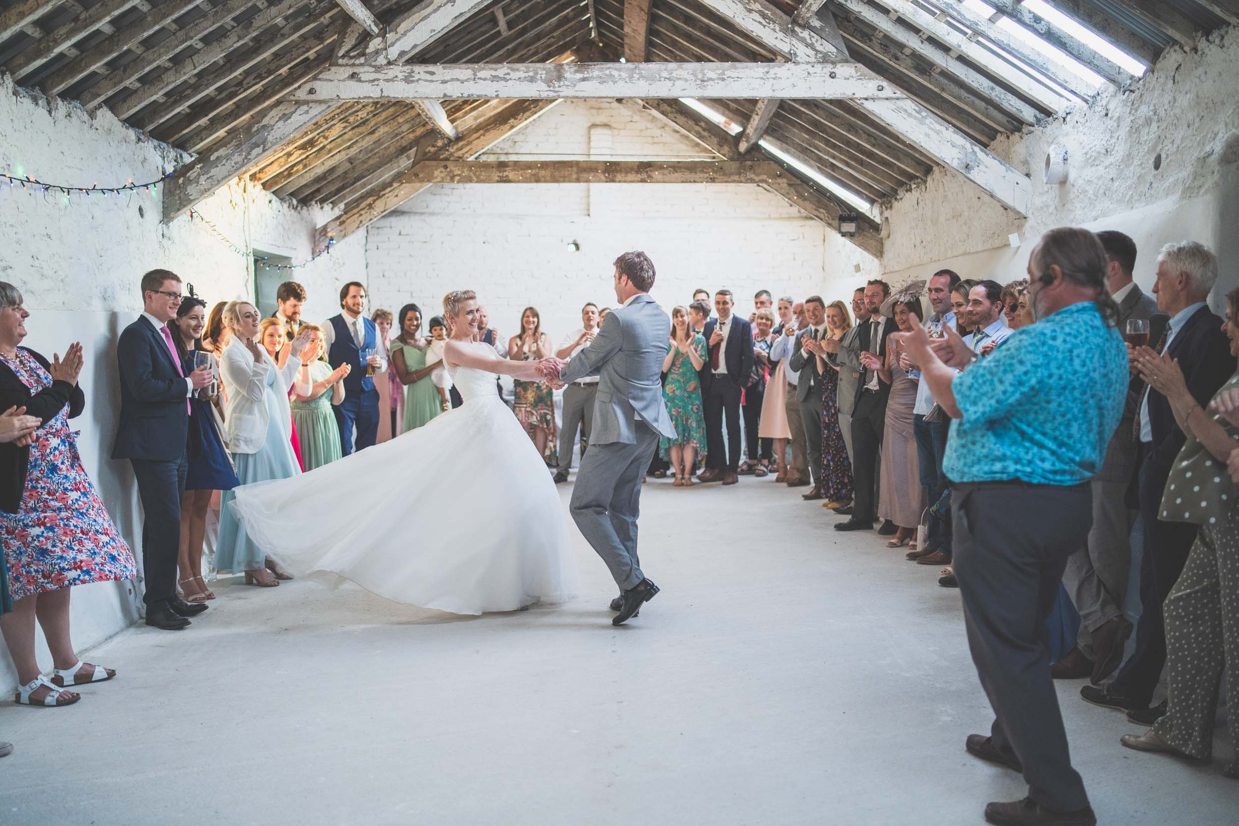 Bride, groom and wedding ceilidh band. First dance in a barn in North Wales
