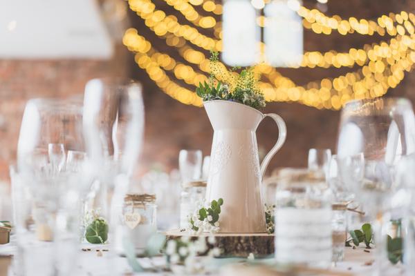 Wedding vase metal jug, lights and bokeh with flowers. Wedding table decorations looking stunning