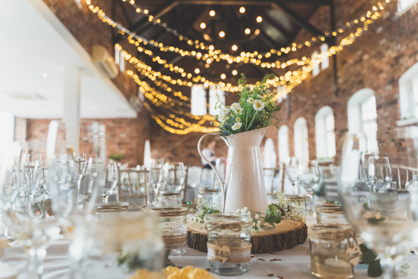 A wider view of the wedding reception room. Flowers, tables, lights, bokeh, vases…. ALL the beauty