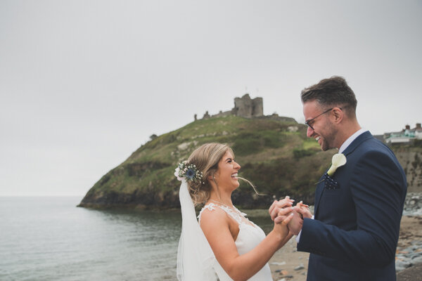 Smiles and laughs on a wedding day wander to the beach…. A little peek of Criccieth castle in the background.