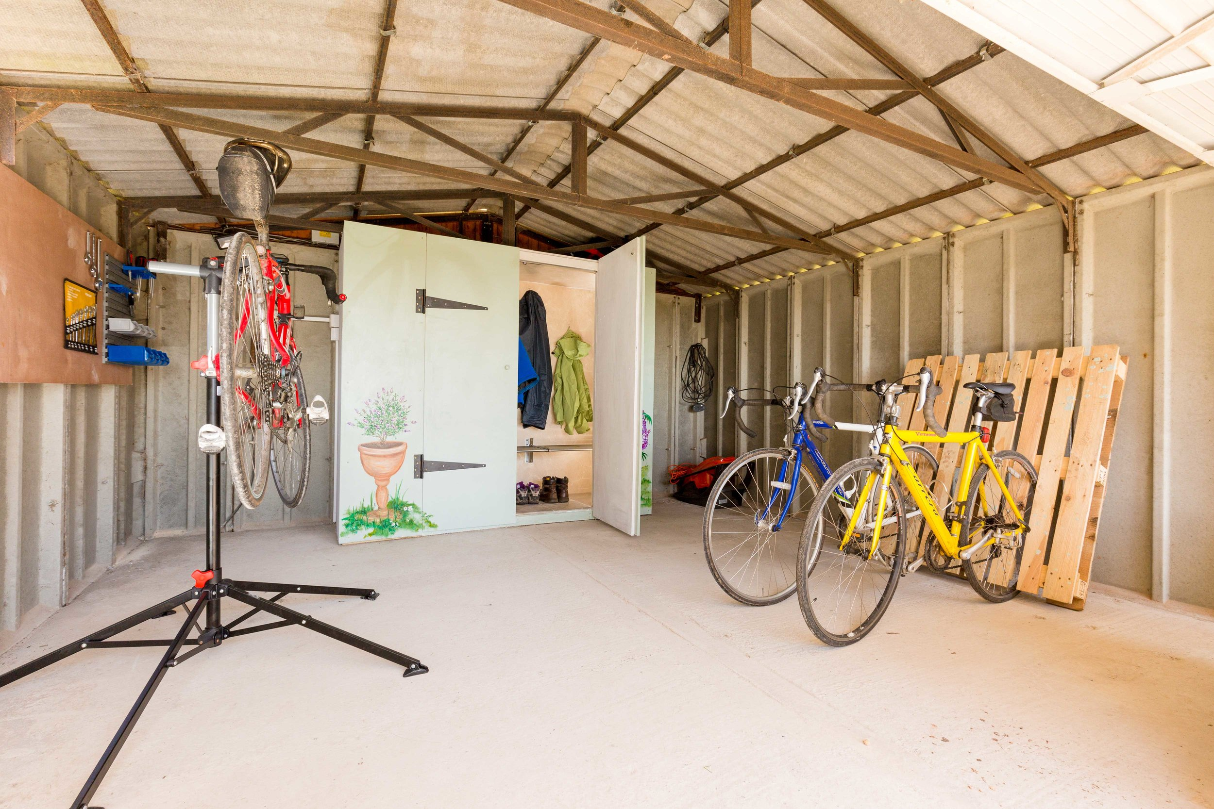 The shed includes a heated drying cupboard for wet weather gear, together with a bike workstation, tools and bike racks...