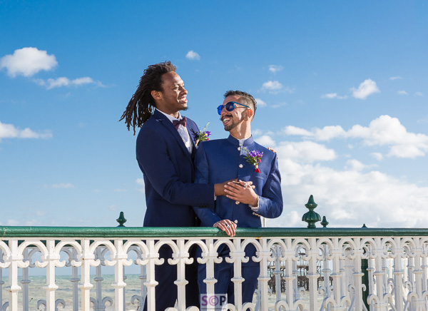 same sex couple laughing together at brighton bandstand