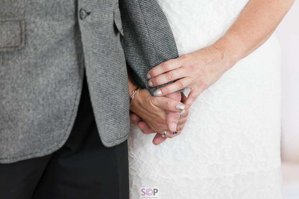 bride using two hands to hold grooms hand during service close up