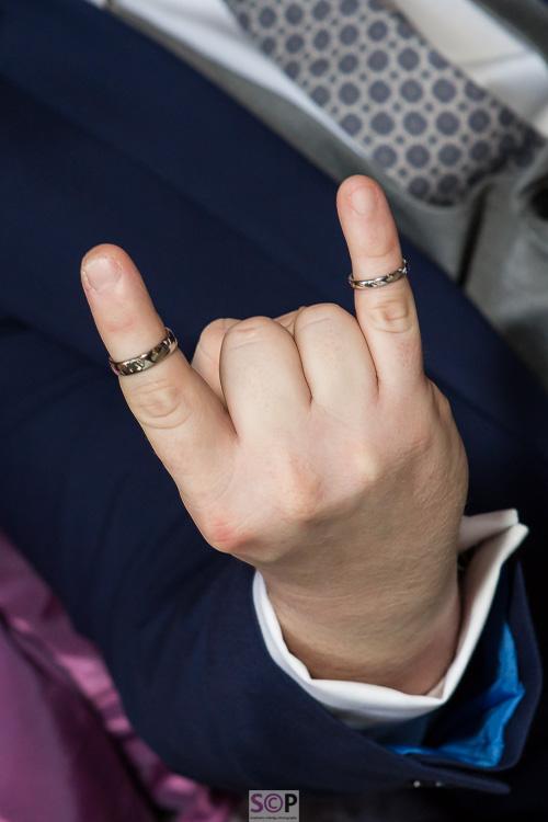 wedding rings on hand making devil horns