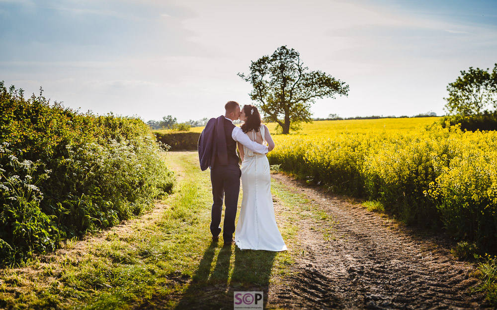 beautiful bride and groom kissing on a track by yellow rapeseed field.jpg