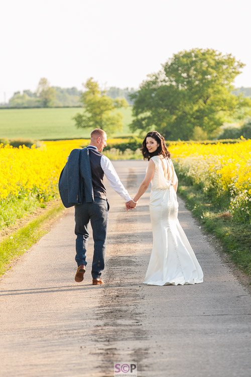 bride and groom holding hands with her looking over shoulder by yellow rapeseed field