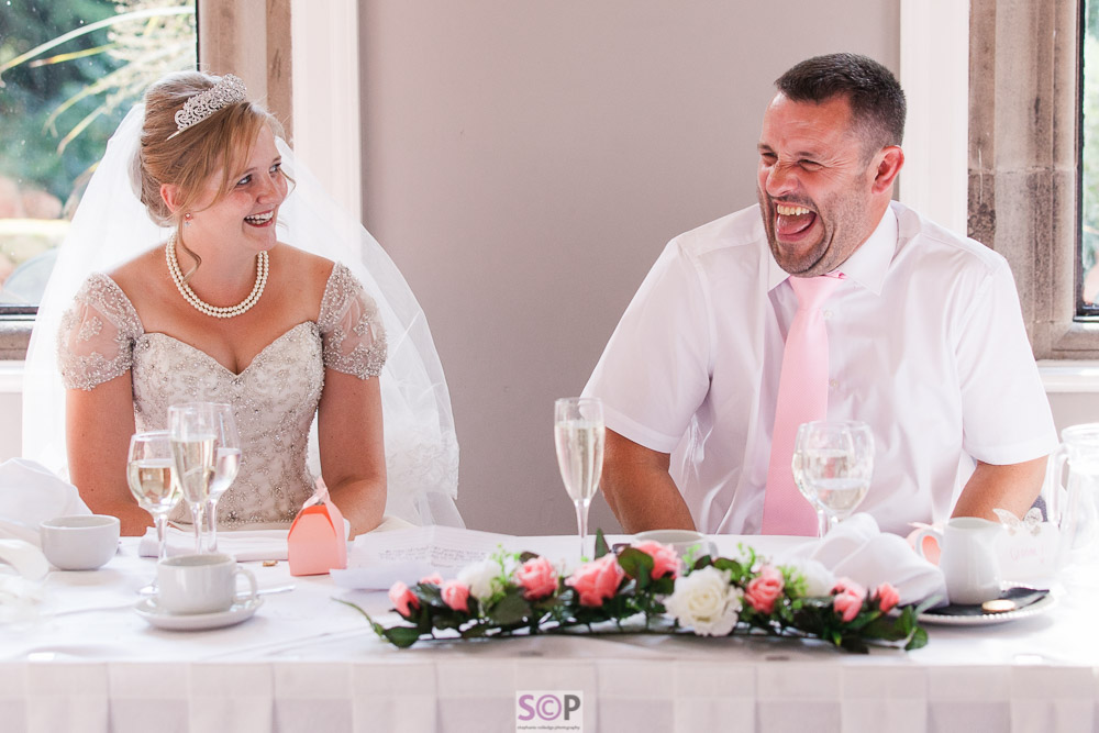 bride and groom really laughing at reception