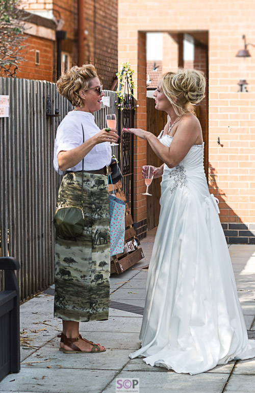Beautiful bride chatting to female guest animatedly