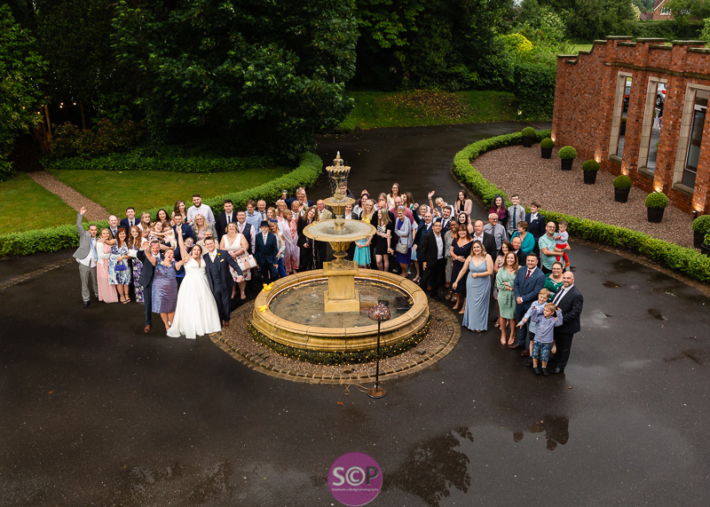 pendrell hall bride groom and guests around the fountain in  the rain