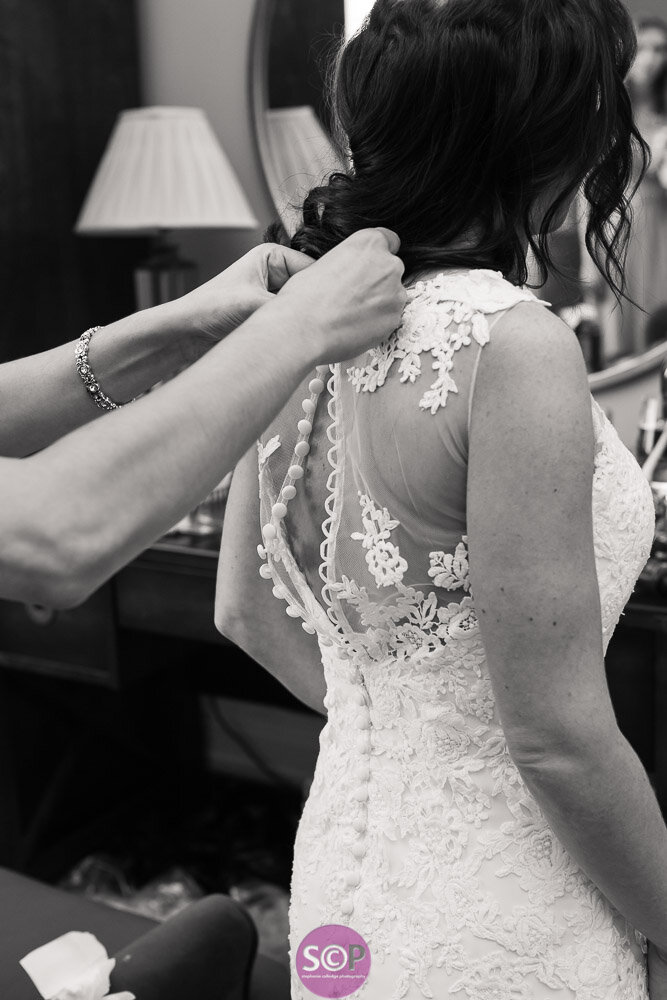 the finishing touches as a bridal dress is buttoned
