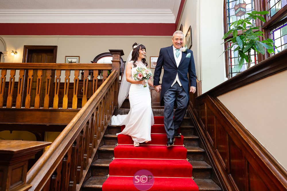 bride and father on the stairs laughing on the way to the service at the iliffe, coventry