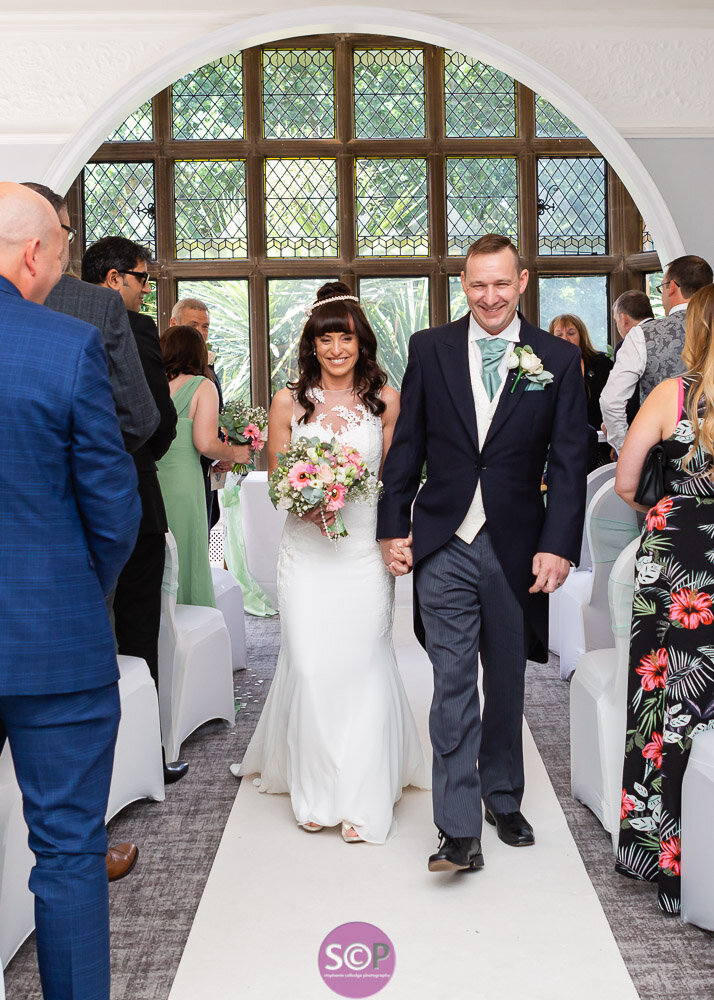 bride and groom walking down the aisle at the iliffe, coventry