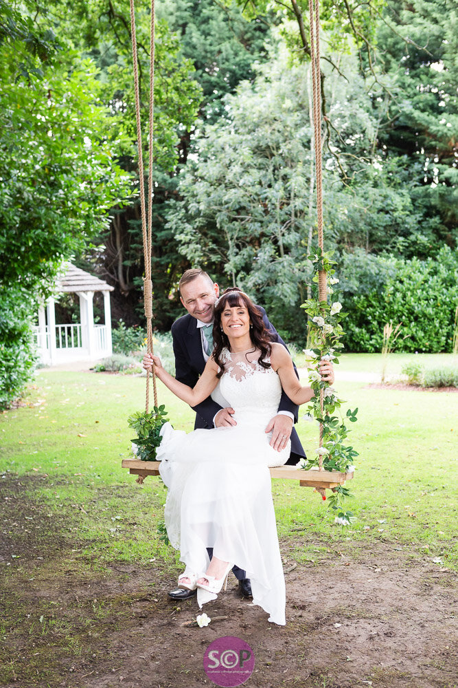 bride and groom on the swing in the grounds of the iliffe in coventry laura ashley hotels