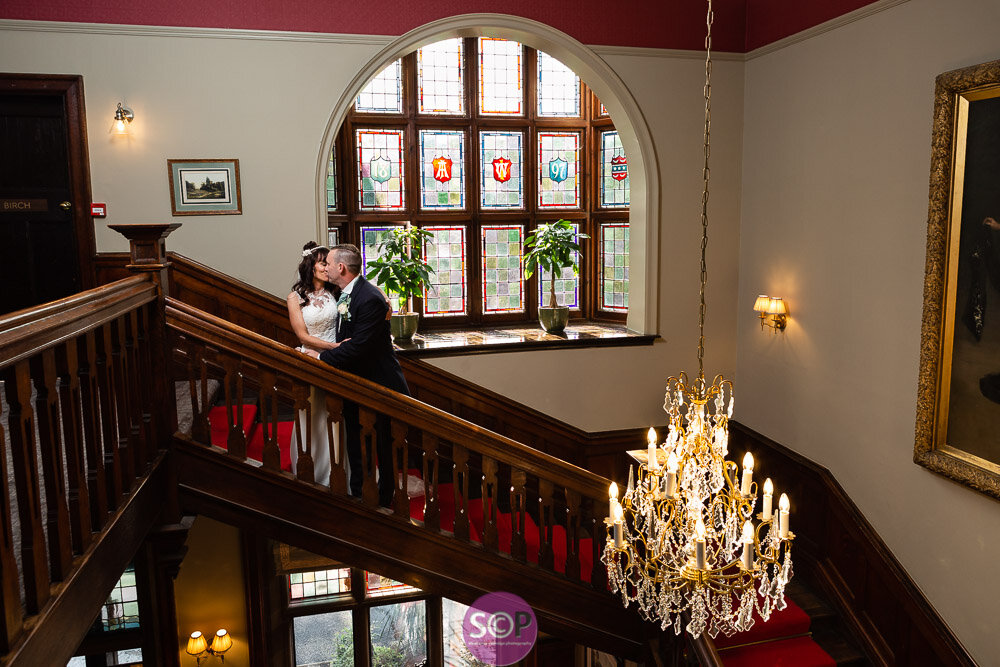 bride and groom on the stairs with chandelier at the ilife in coventry