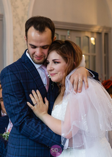 groom holds bride in his arms at the wedding service