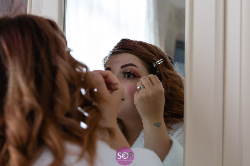 bride looking in mirror to do eye make up