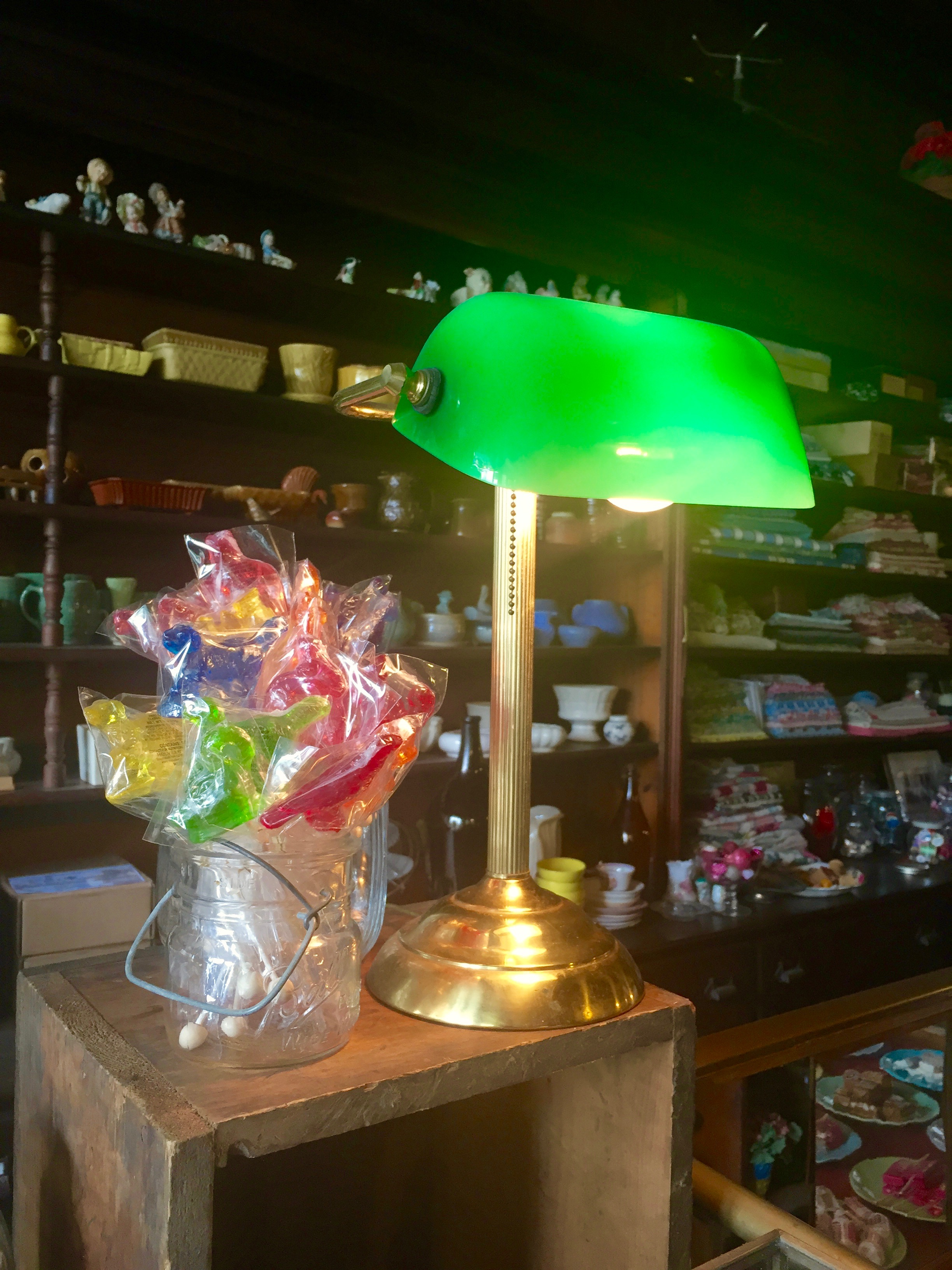 Hand-molded barley sugar lollipops, made by Melville Candy, glow under a banker's lamp.