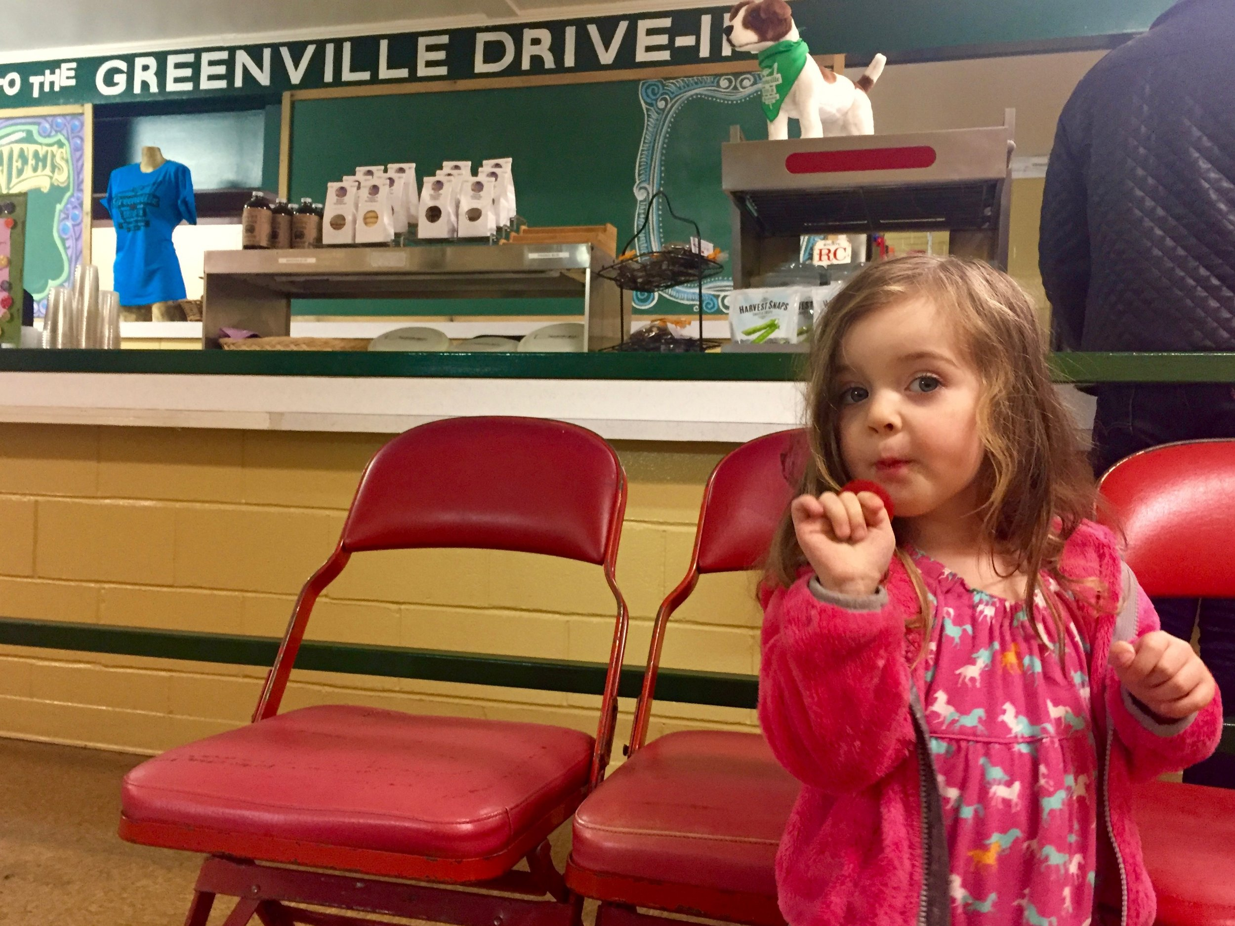 In the Greenville Drive-in concession area, Ramona enjoys a Ring Pop.