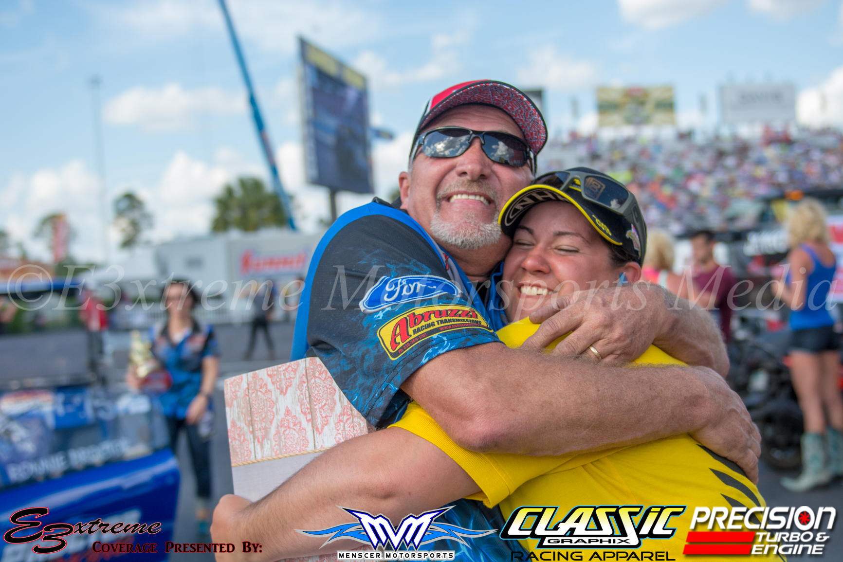Ronnie celebrates the win with the NHRA staging lane woman.