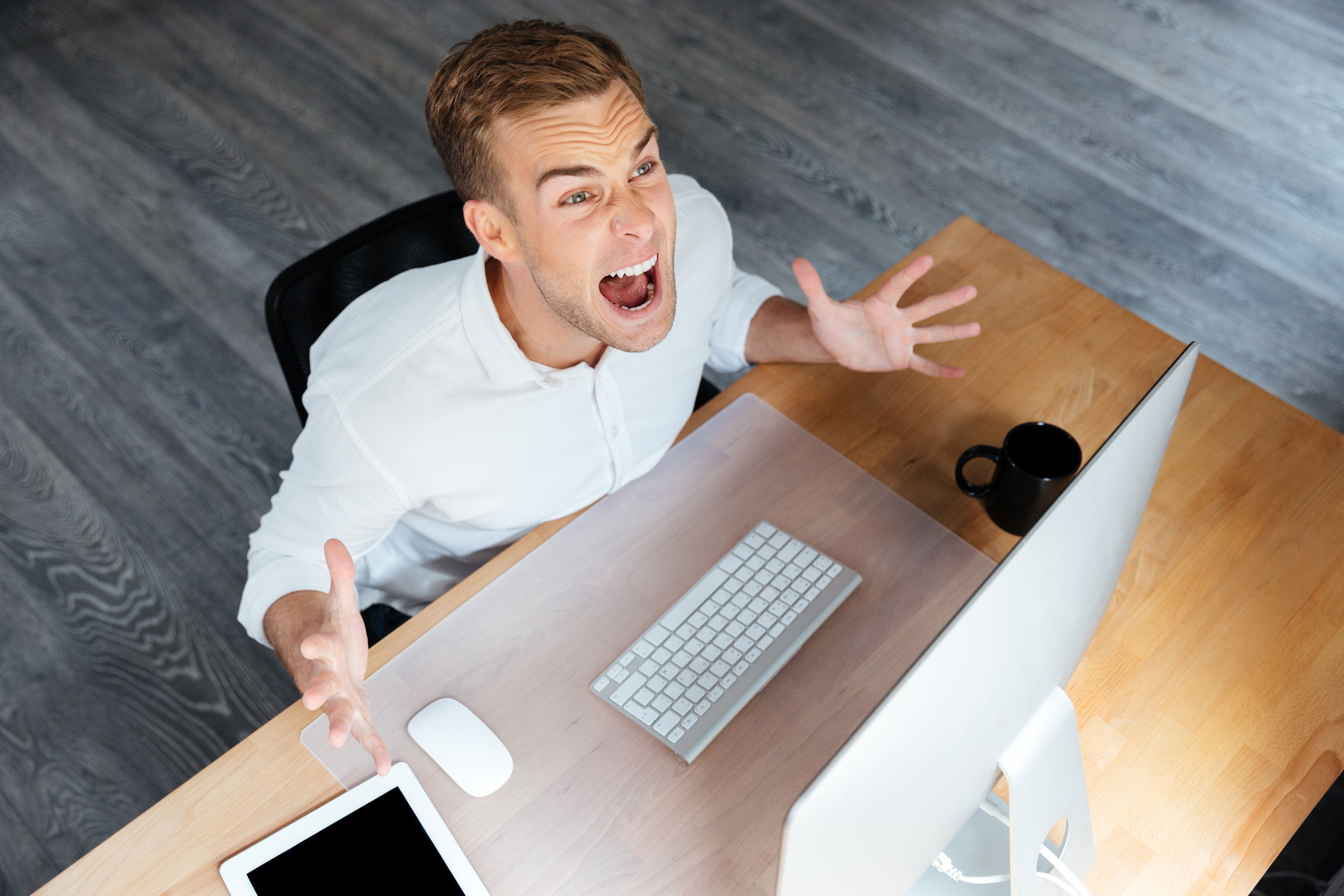 graphicstock-top-view-of-mad-young-businessman-working-with-computer-and-shouting_BdWx2ofB2e.jpg