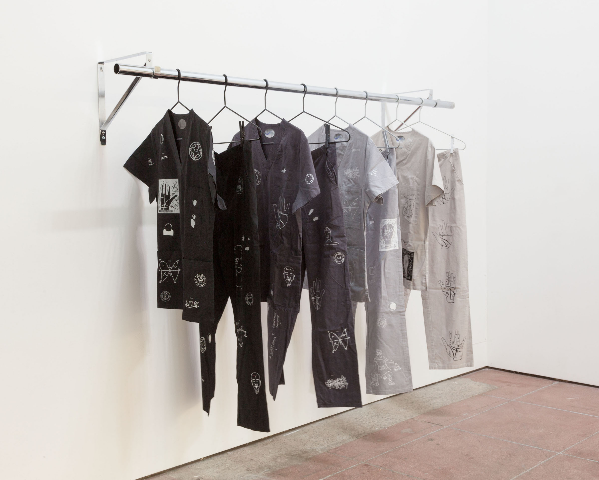 Natalie Labriola, Uniforms For Psychic Protection , 2015,powder coated steel hangers, painted clothes pins, custom made heat-pressed cotton garments, chrome garment rack, dimensions variable