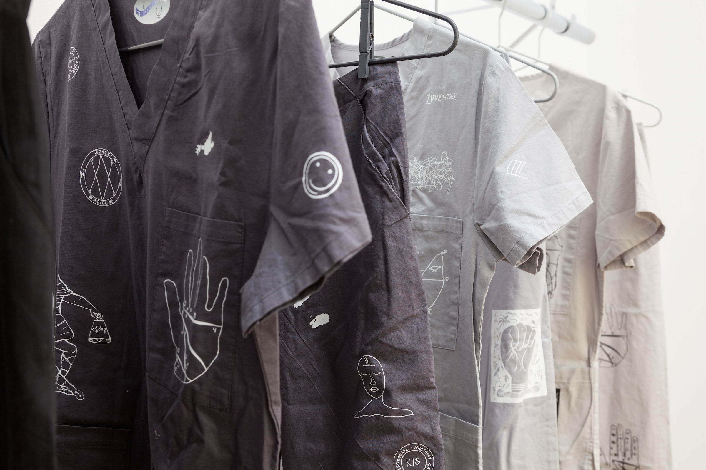 Natalie Labriola, Uniforms For Psychic Protection  (detail), 2015,powder coated steel hangers, painted clothes pins, custom made heat-pressed cotton garments, chrome garment rack, dimensions variable