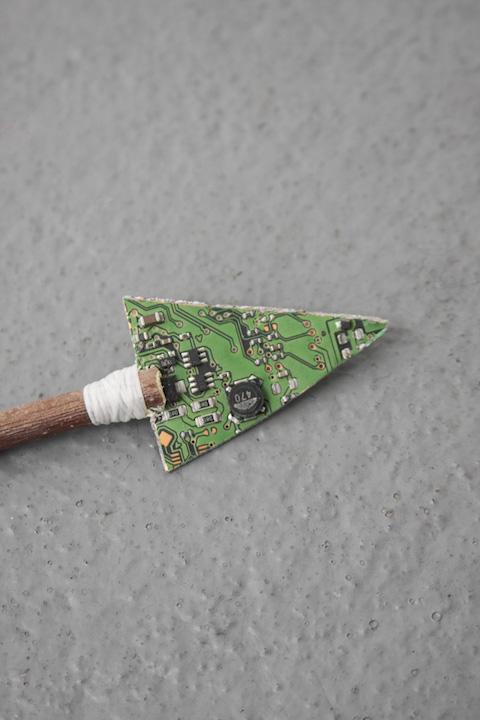 Bea Fremderman, Weapon No. 2 (arrow) (detail),  2017, motherboard, dental floss, branch,19 x 1 in