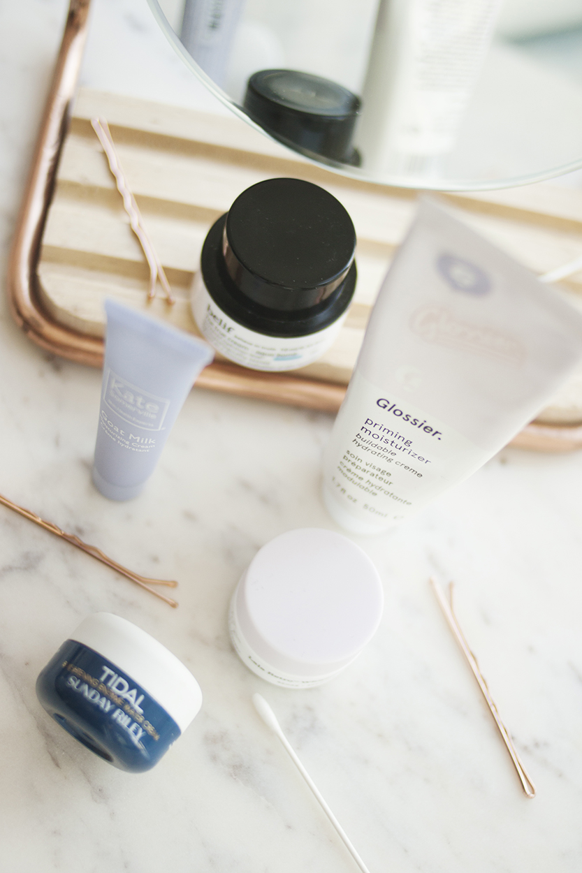 """Glossier Priming Moisturiser - The Glossier Priming Moisturiser is next as it's the one that's most similar in texture to the Goat Milk Moisturising Cream, although this isn't quite as runny. Glossier is still hard to get your hands on in most parts of the world, but of the products I'm talking about in this post, this is the most budget friendly. At $27 CAD for 50ml it won't break the bank (unless you have to pay hefty customs duties or worry about mail forwarding, of course). It contains hyaluronic acid to help with hydration, as well as vitamins A, C & E, although they're pretty far down the ingredients list, which implies to me that they're in a pretty low concentration and probably aren't going to do very much. The inclusion of a retinoid (retinyl palmitate – the vitamin A) is a strange one to me - is it in such a small amount that they don't expect it to do anything - in which case, why bother? Or is it expected to work - in which case, why is it in a moisturiser intended for daily use when we're always told to use retinoids at night? I haven't personally experienced any problems using this, but that's definitely something that doesn't make sense to me.They claim it has an """"anti-redness complex"""", but I don't find that this has any effect on my redness. It's also supposed to include an """"oxygenating agent"""" that delivers oxygen to your skin cells and improves texture, which I don't buy at all. Frankly, I don't see how oxygen and texture are linked, or what ingredient that is from the ones listed. I also think my skin can get its own oxygen just fine."""