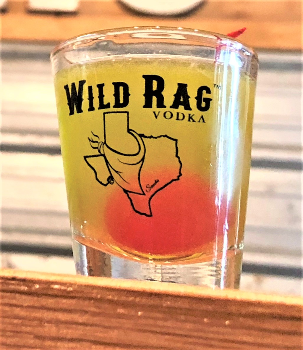 MINI CLOVER SHOT   In a shaker Add ice 1 shot of Wild Rag Vodka or Wild Rag Mesquite Bean Vodka 1/2 oz green simple syrup 1/2 oz triple sec Squeeze of lime Shake well and pour Garnish with a cherry.