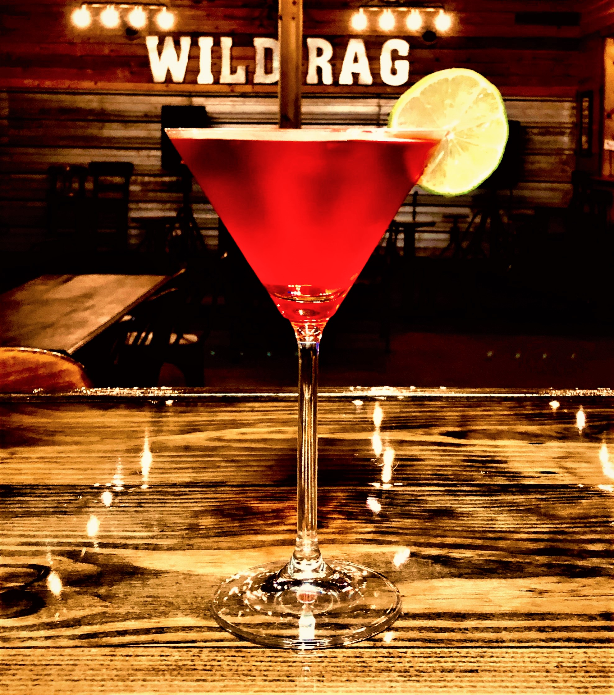 WRV COSMO   Chilled glass Add 1.5 shot of WILD RAG VODKA or WILD RAG MESQUITE BEAN VODKA 1/2 oz of triple sec Fill with Cranberry juice A squeeze of lime Garnish with a key lime slice.